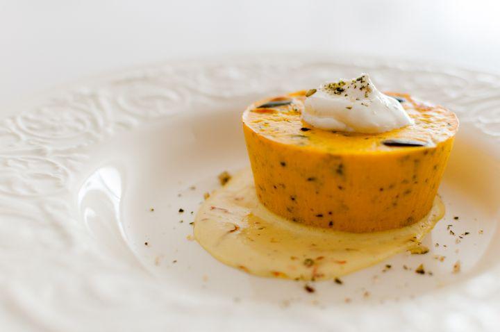 Tortino di zucca su crema di zafferano e ciuffo di formaggio fresco