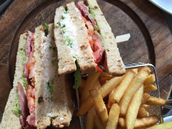 Club sandwich con il granchio, avocado e pancetta accompagnato dalle patatine fritte